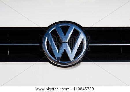 MALAGA, SPAIN - DECEMBER 2, 2015: Volkswagen car front logo over white paint. Volkswagen Group cars are involved in a violation of the CO2 emissions law through an illegal software.