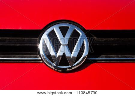 MALAGA, SPAIN - DECEMBER 2, 2015: Volkswagen car front logo over red paint. Volkswagen Group cars are involved in a violation of the CO2 emissions law through an illegal software.