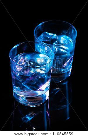 Two Glasses With Vodka And Ice Cubes Against The Background Of Deep Blue Glow On Dark Mirror