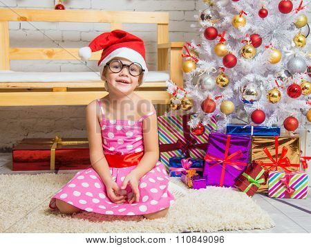 Girl In The Red Hat And The Funny Round Glasses On A Rug In A Christmas Setting
