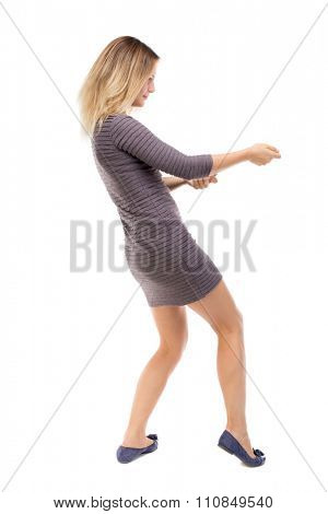 back view of standing girl pulling a rope from the top or cling to something. girl  watching.  .  backside view of person.  Isolated over white background. Blonde in a short dress pulls the rope.