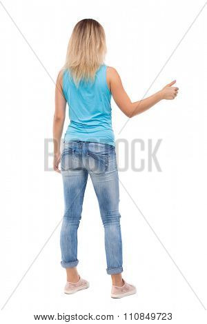 Back view of  woman thumbs up. Rear view people collection. backside view of person. Isolated over white background. blonde in a blue t-shirt and jeans with his right hand shows the thumb.