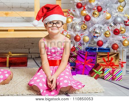 Girl In The Red Hat And The Funny Round Glasses Sits On The Mat At The Christmas Trees
