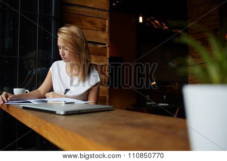 Young beautiful woman reading magazine during coffee break in cafe