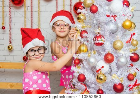 Two Funny Girls Hanging Balls On The Christmas Tree