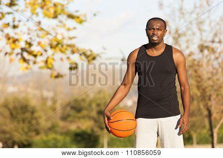 Afroamerican man street basket player holding a basketball outdoors