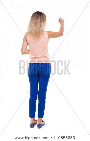 back view of writing beautiful woman. Rear view people collection.  backside view of person. Isolated over white background. Blonde in blue trousers draws felt-tip pen in front of you on the board.