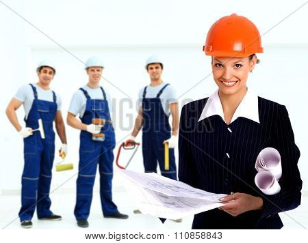 Female architect holding blueprints at the background of the decorators