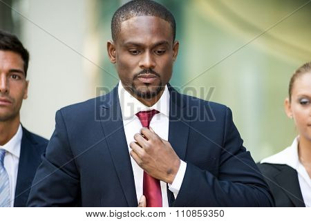 Portrait of an african businessman adjusting his necktie
