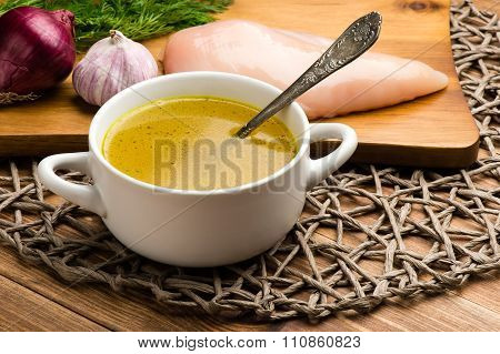 Chicken bouillon in the white bowl on the rustic wooden background.