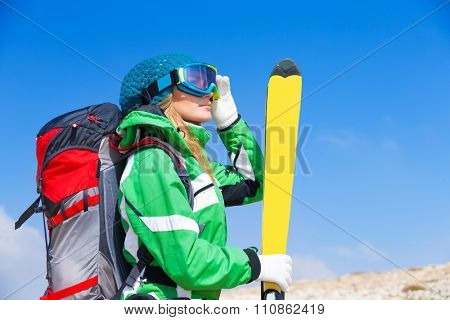 Beautiful ski instructor, woman wearing mask and sportive outfit holding in hand ski over blue sky background, active winter holidays
