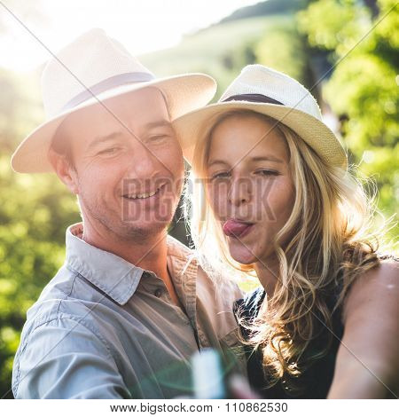 Young couple in love taking self portrait outdoor, woman grimace