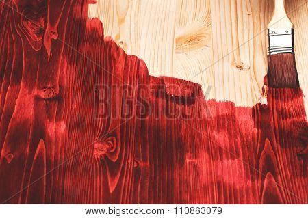 Hand painting red color on wooden table