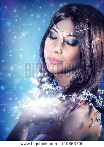 Portrait of beautiful princess looking on magical glowing light on her hand, Christmas miracle, fashion look for winter holidays