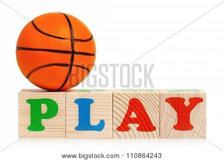 Wooden blocks arranged in the word PLAY and small basketball ball - isolated on white background