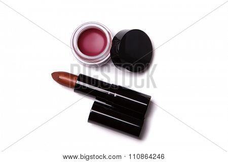 Top view of metallic red lipstick and lip gloss in jar, isolated on white background