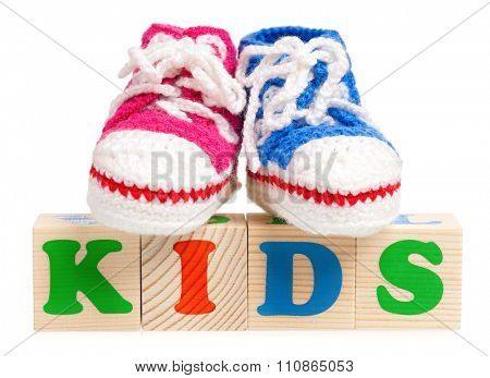 Kids word formed by wood alphabet blocks with booties for baby, isolated on white background