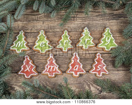Christmas framework arranged from spruce branches placed on wooden rustic boards with decorative seasonal shape gingerbread cookies spelling Merry Xmas