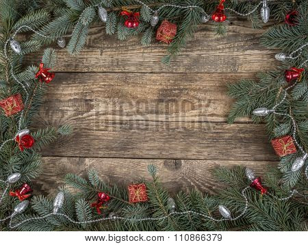 Christmas framework arranged from spruce branches and seasonal decorations placed on wooden rustic boards with copy space