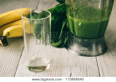 Smoothies In A Food Processor, Glass, Banana And Spinach On A White Wooden Background
