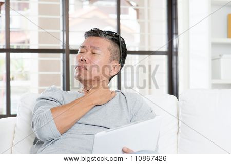 Portrait of 50s mature Asian man neck pain, pressing on shoulder with tired expression after long period using tablet computer, sitting on sofa at home.