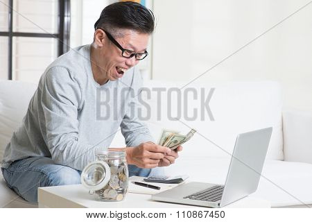Mature 50s Asian man counting on money with excited face expression. Saving, retirement, retirees financial planning concept.