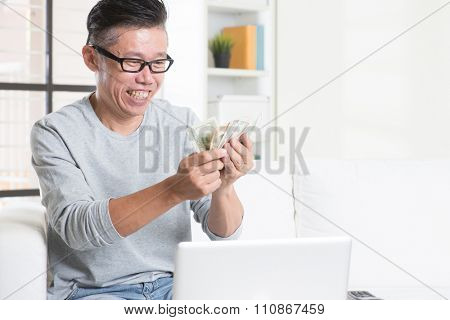 Portrait of 50s mature Asian man counting cash, earning money from his successful online business. Working from home concept.
