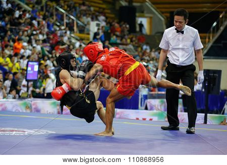 JAKARTA, INDONESIA: NOVEMBER 14, 2015: Gunawan from Indonesia (red) fights Lam Man Kan from Hong Kong (black) in the men's 52kg Sanda (kick-boxing) event at the 13th World Wushu Championship 2015.