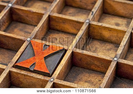 letter X abstract - vintage letterpress printing block stained by red ink in a grunge wood typesetter box with dividers
