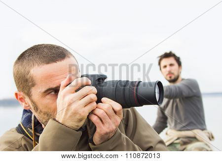 Men in boat on the river, taking photos with camera, adventure, real