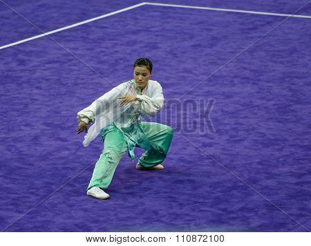 JAKARTA, INDONESIA: NOVEMBER 14, 2015: Sanatombi Leimapokpam from India performs the movements in the women's Taijiquan event at the 13th World Wushu Championship 2015 in Istora Senayan, Jakarta.