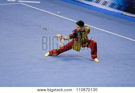 JAKARTA, INDONESIA, NOVEMBER 14, 2015: Jason Chen-Leung from Canada performs the movements in the men's Jianshu (sword) event at the 13th World Wushu Championship 2015 held in Istora Senayan, Jakarta.