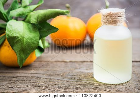 Tangerine Oil In A Glass Bottle With Fresh Tangerines