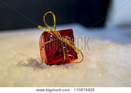 Red gift box with a golden ribbon in top of snow for christmas decoration or to put under the tree