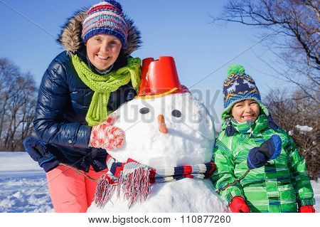 Boy and his mother with a snowman