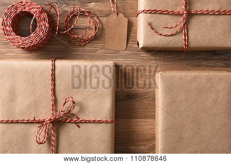 Christmas presents wrapped with eco friendly and recyclable paper and cord. High angle closeup in horizontal format.