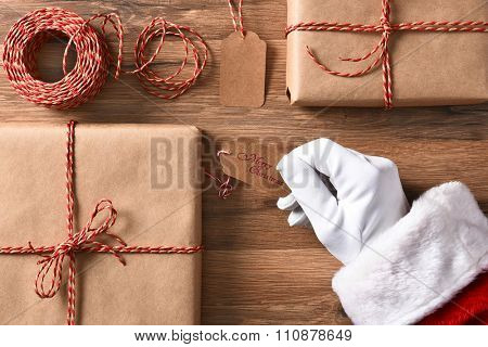 High angle view of Santa Claus hand holding a gift tag with Merry Christmas. Closeup with wrapped presents and string.