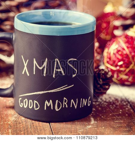 text xmas good morning written in a black mug with coffee or tea on a rustic wooden table with some pinecones and red christmas baubles