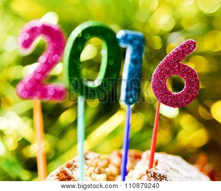 closeup of four glittering numbers of different colors forming the number 2016, as the new year, with the focus on the 6, topping a cake