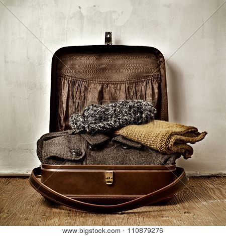 an old brown suitcase with some warm clothing, such as an overcoat, a scarf and a knit cap