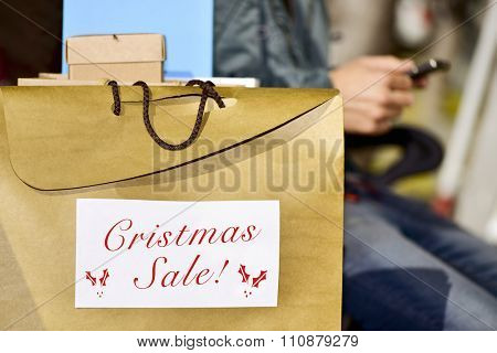 closeup of a young caucasian man sitting in a bench using his smartphone with some shopping bags, one of them with the text happy christmas sale written in it
