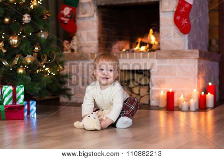 Kid playing with toy gift on Christmas eve at fireplace.. Decorated living room with traditional fir
