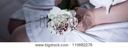 Abused Female Holding Bloody Rose