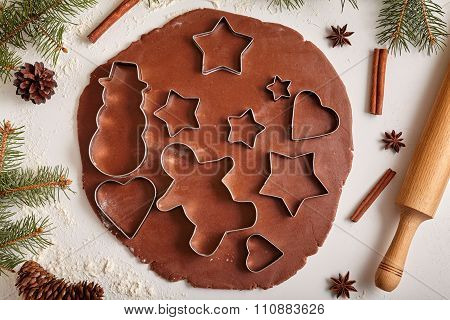 Gingerbread cookies dough preparation recipe with man shape, heart, fir trees, snowman and star form