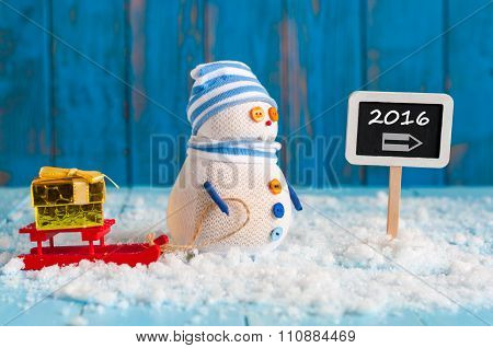 New Year 2016 is coming concept. Snowman with red sled and xmas giftnear roadsign 2016. Christmas, n