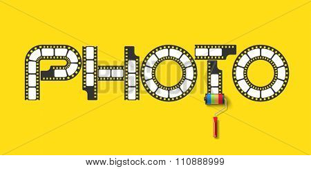 Lettering PHOTO from photo film tape with roller brush from photo reel on yellow background