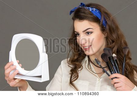 The Beautiful Young Woman Looks In A Mirror