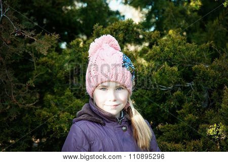 Adorable Little Girl Posing Near The Branch Of Tree .