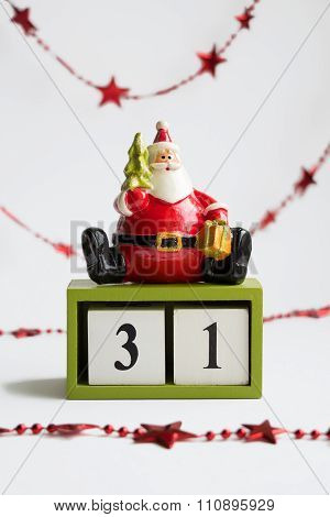 Santa Claus Sitting On Cubes Showing The Date thyrty first On White background with red garland