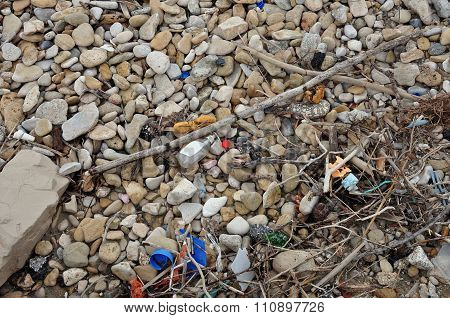 Plastic And Driftwood On Stone Beach